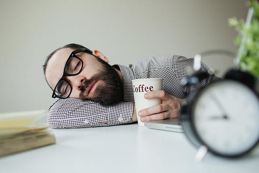 Мужчина уснул в офисе за рабочим местом прямо находу со стаканом кофе.