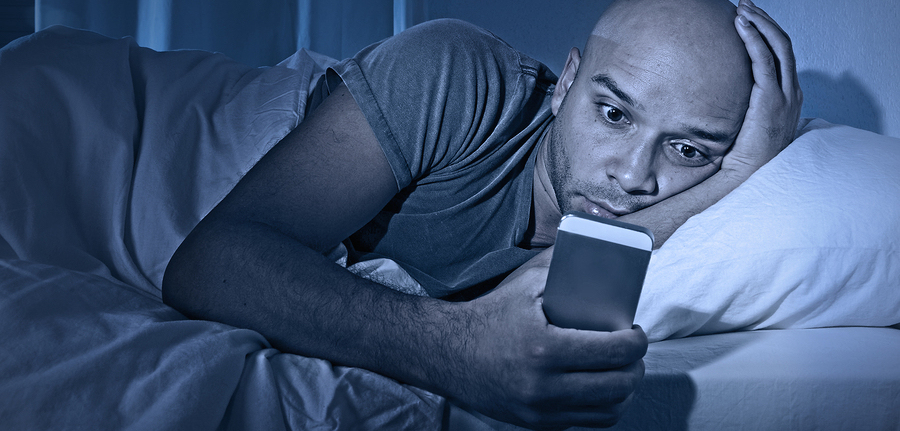 young cell phone addict man awake at night in bed using smartphone for chatting flirting and sending text message in internet addiction and mobile abuse concept